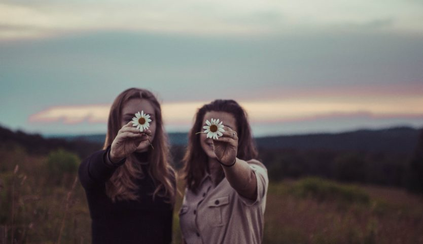 two-female-friends-holding-up-flowers