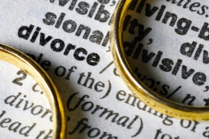 "Two separate wedding rings next to the word ""divorce"""