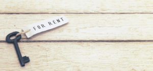 Black-key-with-a-for-rent-tag-sitting-on-wood