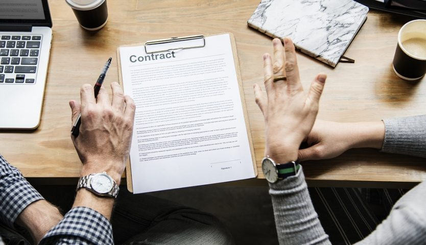 two sets of hands talking over a contract