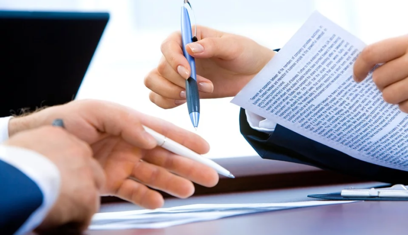 lawyer-signing-papers-with-client