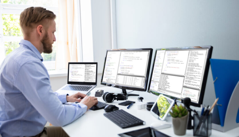 man working at desk with 3 monitors