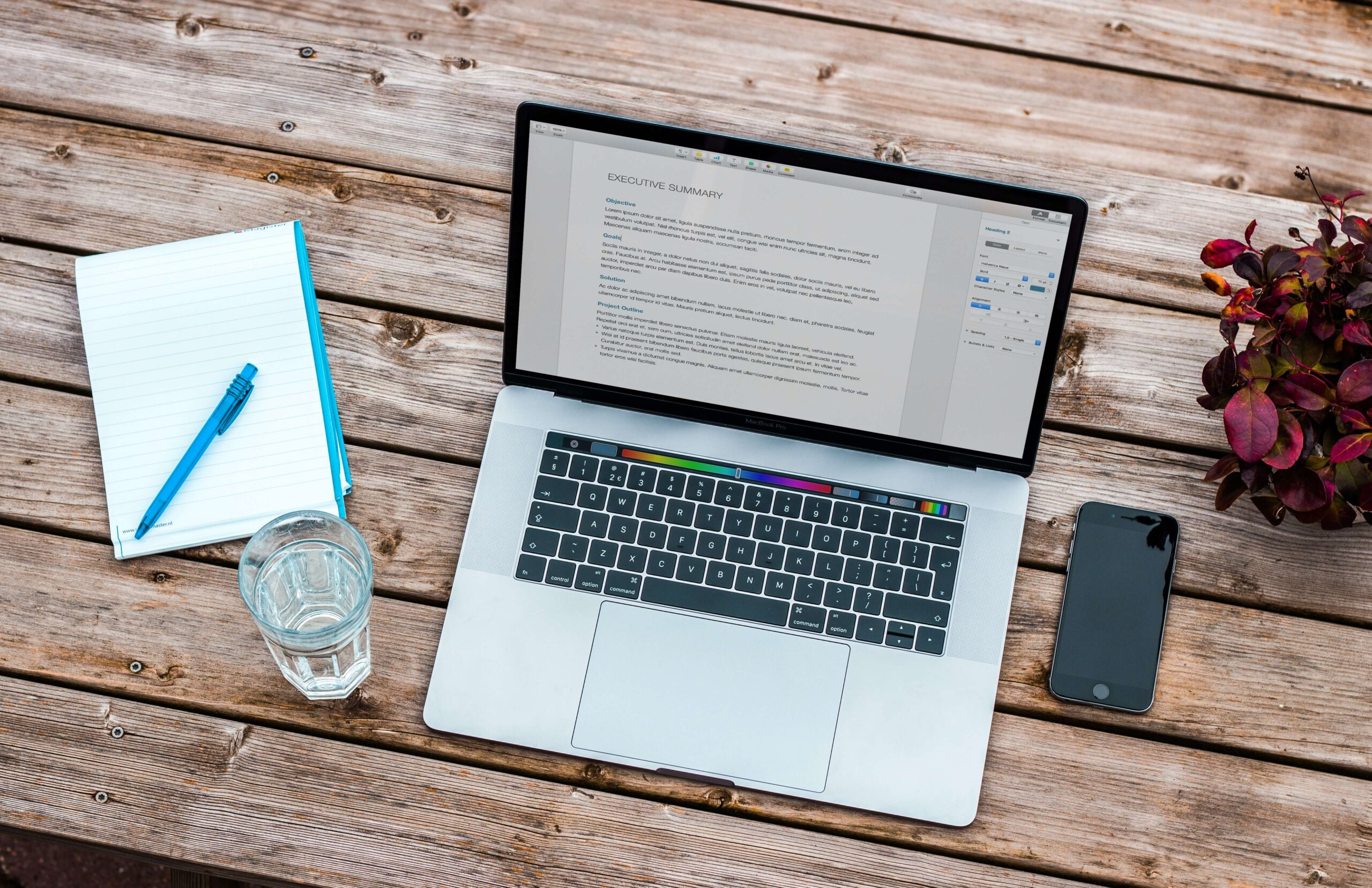 silver macbook and gray iphone and clear drinking class on brown wooden table top