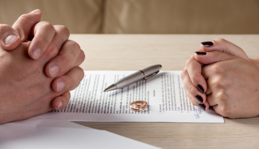 hands clasped over signed divorce papers with pen and rings