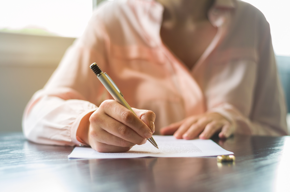 young woman signing divorce agreement