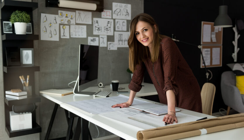 woman with long brown hair standing over drafting table