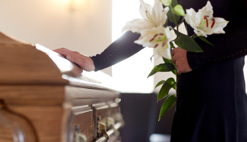 person in a black long sleeve top holding white lilies putting one hand on a brown casket.