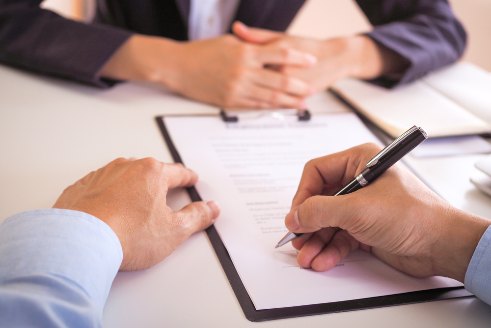 man signs document with lawyer
